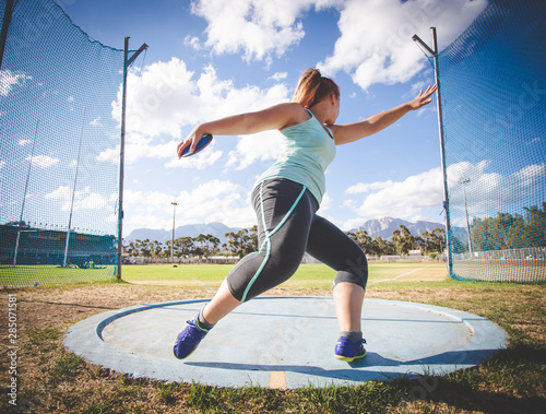Fotografia, Obraz  Wide angle action photo of a female discus athlete throwing a discus