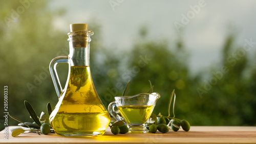 Olive oil bottle on wooden table, natural oils concept