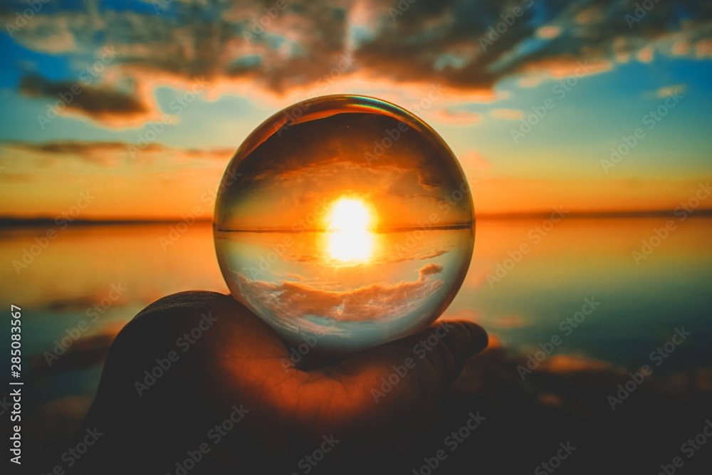 Fototapeta Creative crystal lens ball photography of the sunset with clouds blurred in the background