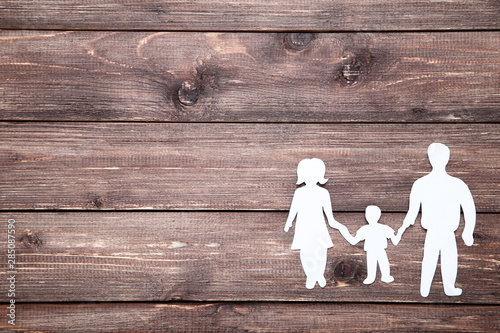 Obraz Family figures on brown wooden table - fototapety do salonu