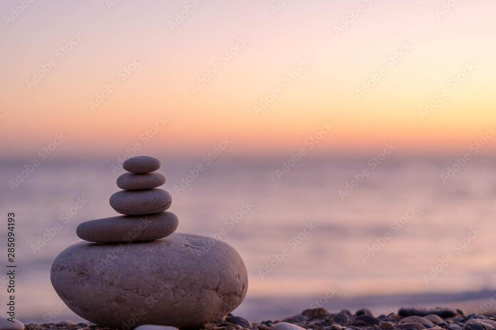 Fototapeta Perfect balance of stack of pebbles at seaside towards sunset. Concept of balance, harmony and meditation. Helping or supporting someone for growing or going higher up.