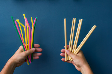 One hand holds colourful plastic straws and another hand holds bamboo straws. Good background for ecology topics.