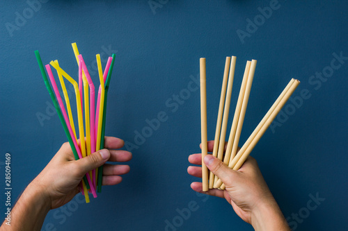 One hand holds colourful plastic straws and another hand holds bamboo straws Fototapeta
