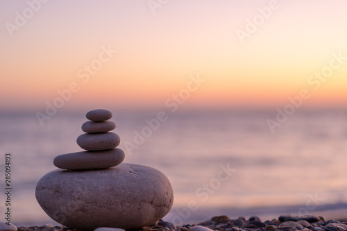 Obraz Perfect balance of stack of pebbles at seaside towards sunset. Concept of balance, harmony and meditation. Helping or supporting someone for growing or going higher up. - fototapety do salonu