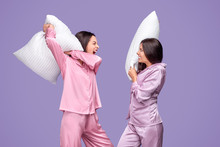 Young Women Having Pillow Fight During Sleepover