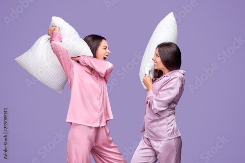 Cuadros en Lienzo Young women having pillow fight during sleepover