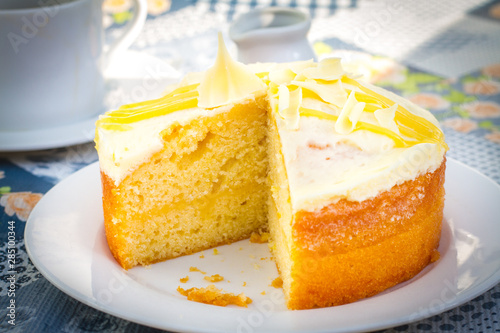 Photo Lemon drizzle sponge cake with white icing and chocolate flakes on top and lemon curd and sponge filling on a white plate