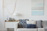 Abstract paste blue and white painting on empty white wall behind beige couch with pillows - 285100785