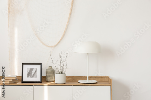 Obraz White industrial lamp, photo in frame and plant in pot on wooden console table in elegant living room with white wall - fototapety do salonu