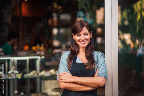 Obraz Portrait of a beautiful positive waitress standing in the doorway - fototapety do salonu