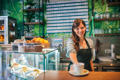 Portrait of a female barista standing behind the bar, serving coffee.