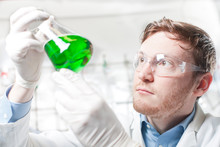 Germany, Young Scientist Checking Green Liquid In Erlenmeyer Flask