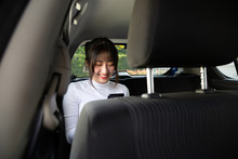 Asian Teenager Woman Using A Smartphone In Back Seat Of Car, Passengers Use An App To Order A Ride And Peer-to-peer Ride Sharing Concept