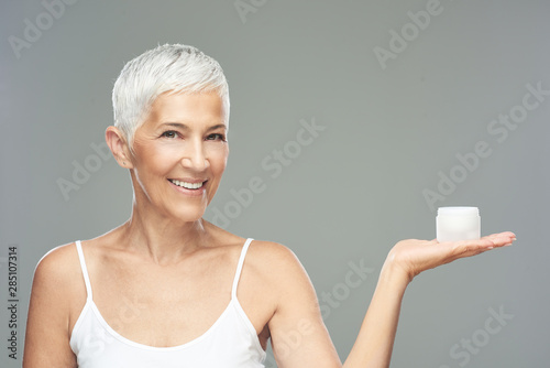Fotomural  Gorgeous smiling Caucasian senior woman trying out new anti age cream and looking at camera