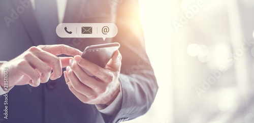 Fotomural CONTACT US, Hand of Businessman holding mobile smartphone with ( mail,phone,email ) icon