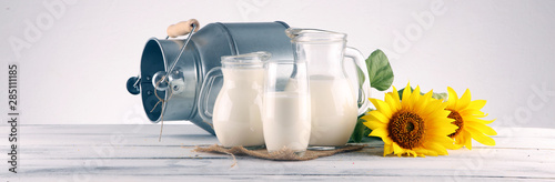 Fototapeta A jug of milk and glass of milk on a wooden table and flower