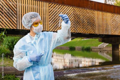 Valokuvatapetti female ecologist or epidemiologist checks water quality in urban river