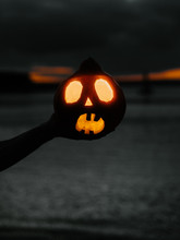 Hand Of Man Holding Halloween Pumpkin