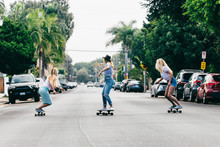 Three Young Anonymous Girls Skateboarding Streets Of Venice California