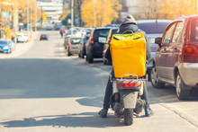 Food Delivery Courier With Big Yellow Backpack Riding Scooter On City Street With Traffic. Fast Lunch Takeaway Delivery. Teenager Job