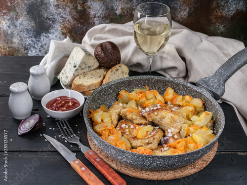 Photo  Chicken meat with stewed curry with vegetables in a pan, cheese, bread and white wine