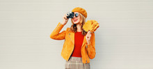 Woman With Autumn Yellow Maple Leaves, Retro Camera Taking Picture In French Beret Over Gray Wall Background