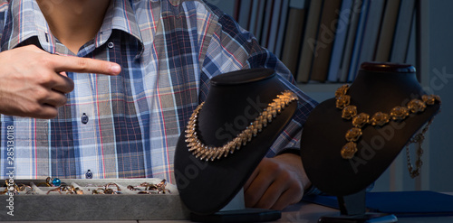 Young male jeweller working at night in his workshop Canvas Print