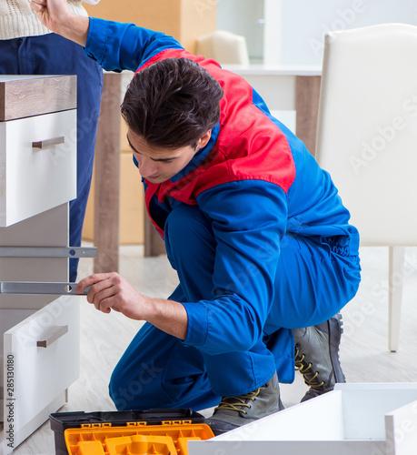 Contractor repairman assembling furniture under woman supervisio Tablou Canvas