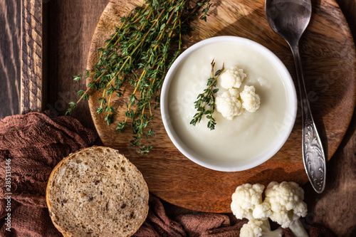 Valokuva Wooden tray with two ceramic bowl with cauliflower cream soup garnish with fresh cauliflower, thyme and bread