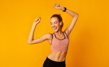 Excited Young Lady In Sportswear Dancing On Yellow Background