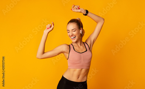 Fotomural Excited Young Lady In Sportswear Dancing On Yellow Background