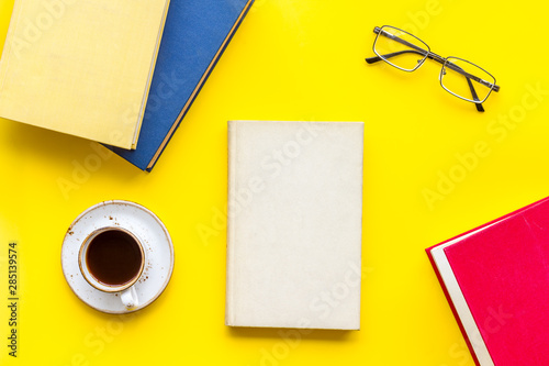 Valokuvatapetti workplace with books, glasses, coffee on yellow background flatlay
