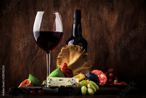 Fotomural  Red wine glass and appetizers, cheese, salami, figs, grapes, vintage wooden tabl