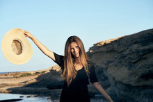 Young Long Haired Smiling Female Model Looking Away Holding Hat In Air On Beach