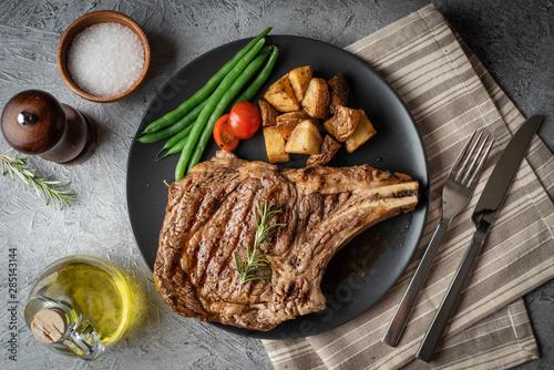 Fotografiet ribeye steak on black plate, concrete background