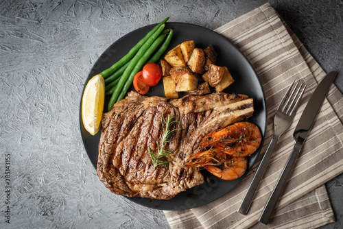 Fotografiet surf and turf, ribeye steak and grilled prawn