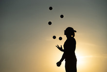 Silhouette Of A Man Juggling With Balls At Sunset