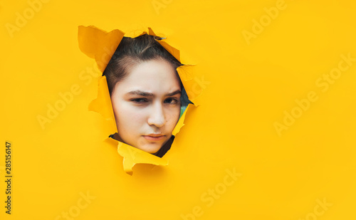 Fotografija  Funny teenage girl peeping through hole on yellow paper