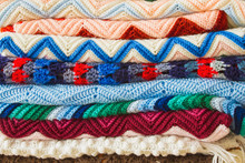 A Colorful Stack Of Folded Crochet Afghans; Cozy, Handmade Crochet Blankets In A Pile