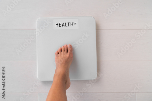 Fotografie, Obraz  Happy weight loss woman stepping on scale weighting healthy weight after diet goal challenge