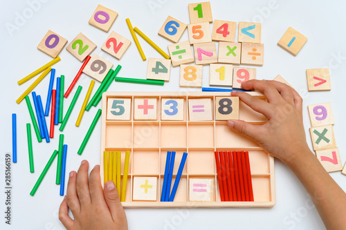 Photo kid doing addition equation using counting rods