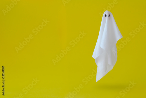 White ghost sheet costume flying in the air with yellow background Canvas Print