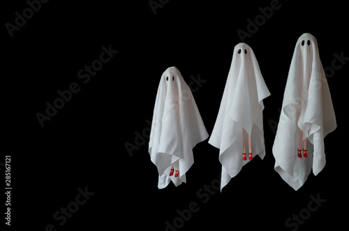 Photo  A group of female ghost white sheet costume flying in the air with black background