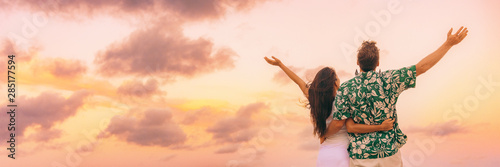 Happy people from behind with arms up to the sky in happiness and joy on summer holiday dusk background sunset panorama tourists couple enjoying vacation Wallpaper Mural