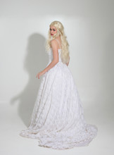 Full Length Portrait Of Blonde Girl Wearing Long White Lace Bridal Gown. Standing Pose On A Studio Background.
