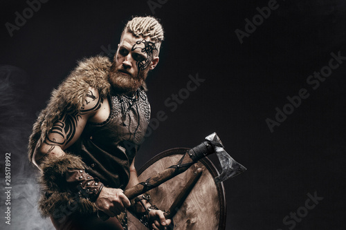 Medieval warrior berserk Viking with tattoo on skin, red beard and braids in hair with axe and shield attacks enemy Canvas Print