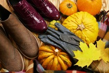 Autumn Fashion Shoes And Accessories. Boots, Gloves, Scarf With Pumpkins And Autumn Leaves On A Wooden Background.Fall Season.