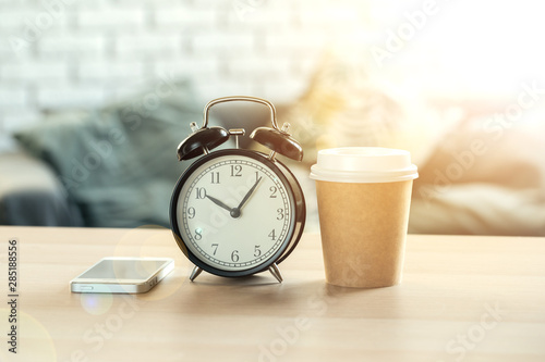 Obraz Classic vintage  alarm clock and  coffee cup on wooden background - fototapety do salonu