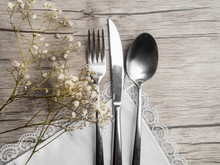 Light Colored Tableware Set: Vintage Silverware On Napkin And Delicate White Flowers On Wooden Background With Copy Space.