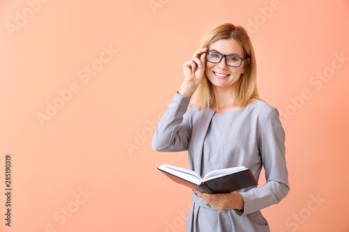 Valokuva Beautiful female teacher with book on color background